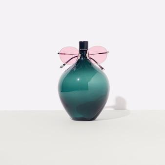 柔らかなパステルカラーの背景にピンクのアイグラスが付いたターコイズ色の花瓶。最小限のコンセプチュアルアート。