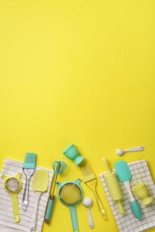 黄色の背景に青緑色の調理器具。食品成分。ケーキを調理し、パンを焼くコンセプト。