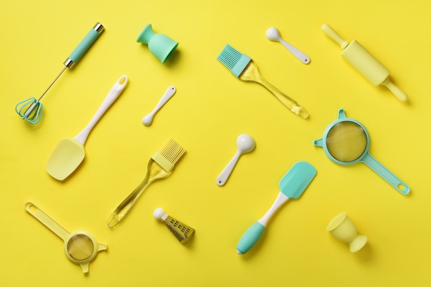 Turquoise cooking utensils on yellow background. food ingredients.