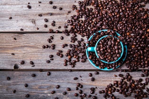木製の背景にコーヒー豆とターコイズブルーのカップ。飲料・食器