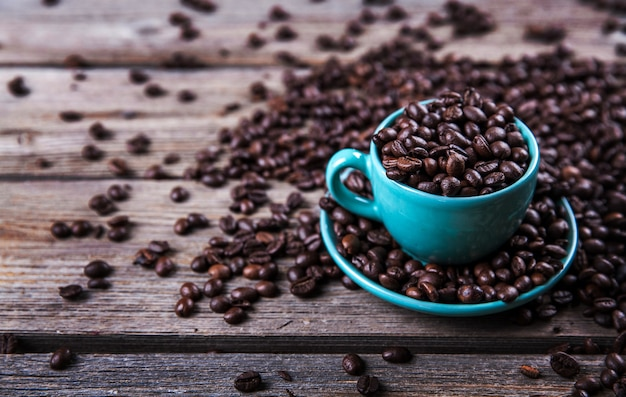 Turquoise cup with coffee beans on a wooden.