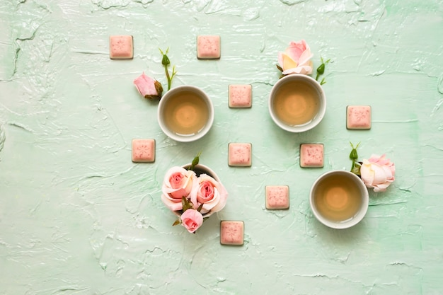 Turquoise cups with rose tea, rose blossoms, pink chocolate on mint