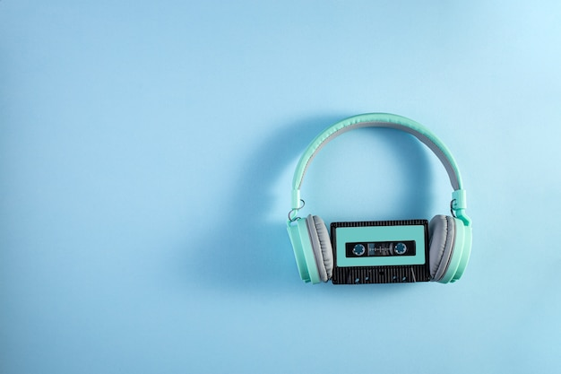 Turquoise headphones with audio cassette on a blue background. music concept
