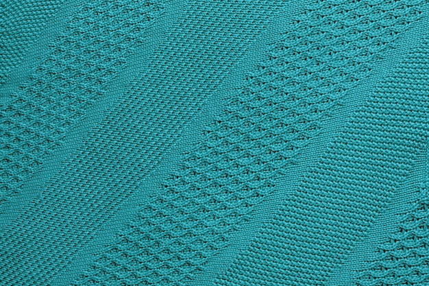 Turquoise knitted plaid closeup.  knitted texture with diagonal ornament.  detailed warm background made of yarn.