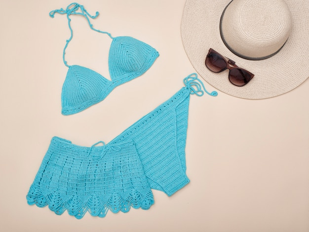 Turquoise knitted swimsuit, hat and sunglasses. beach wardrobe. fashionable concept
