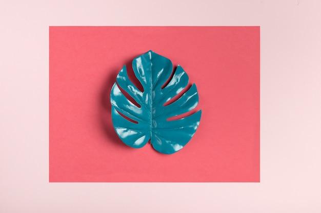 ピンクの背景に青緑色の葉