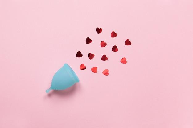 Бирюзовая менструальная чашка на пастельно-розовом фоне с конфетти красных сердечек. изделие женской гигиены