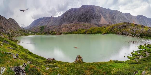 峡谷のターコイズブルーの山の湖。アルタイの劇的な山の風景。雨の高地高原。全景。