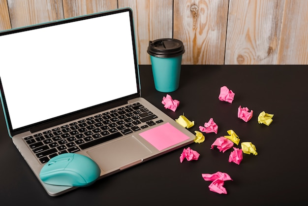 Turquoise mouse; adhesive note; takeaway cup; crumpled paper and laptop showing white screen display on black background