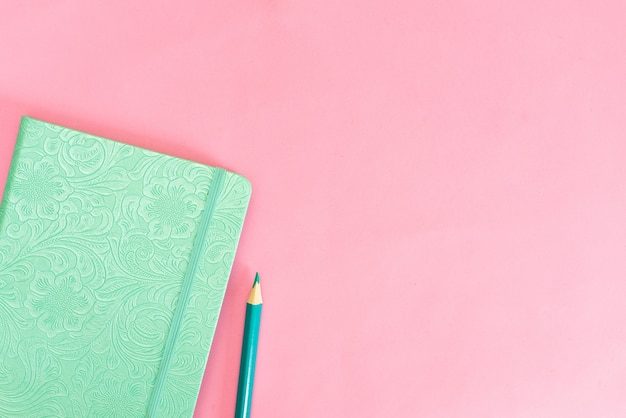 Turquoise notebook on a pink background and pencil.