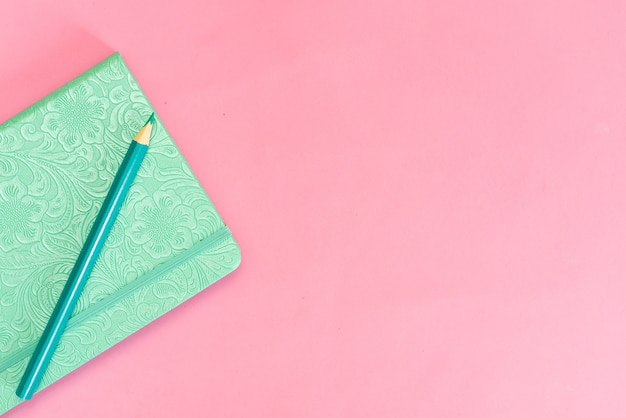 Turquoise notebook on a pink background and pencil