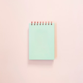 Turquoise notepad on light pink background