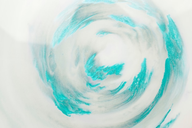 Turquoise paint strokes in swirl pattern over white surface