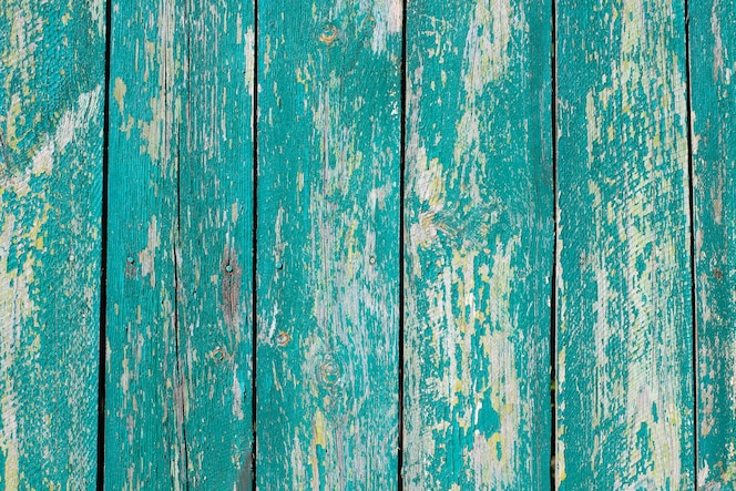 Turquoise painted wooden planks with cracked paint. the nails in the boards. space or texture