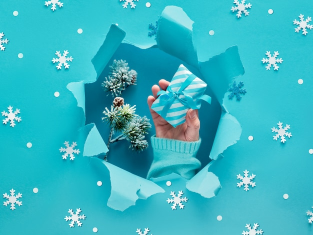 Плоская бирюзовая бумага с рукой, держащей подарок, снежинки и рваное отверстие в середине