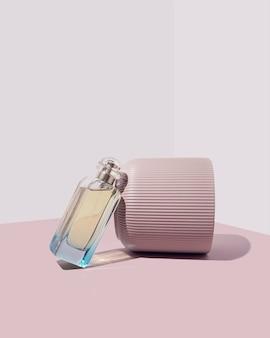 白とグレーの背景にターコイズの香水瓶とパステルピンクの花瓶。モダンなミニマルな美的構成。