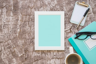 Turquoise picture frame; coffee cup; eyeglasses and clipboard with pen on background