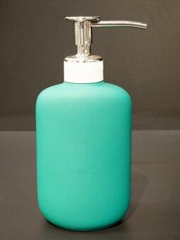 은색 금속 캡과 펌프가 어두운 배경에 있는 청록색 플라스틱 화장품 병, 클로즈업, 비누 용기, 얼굴 크림, 헤어 샴푸, 바디 목욕 젤, 빈 포장
