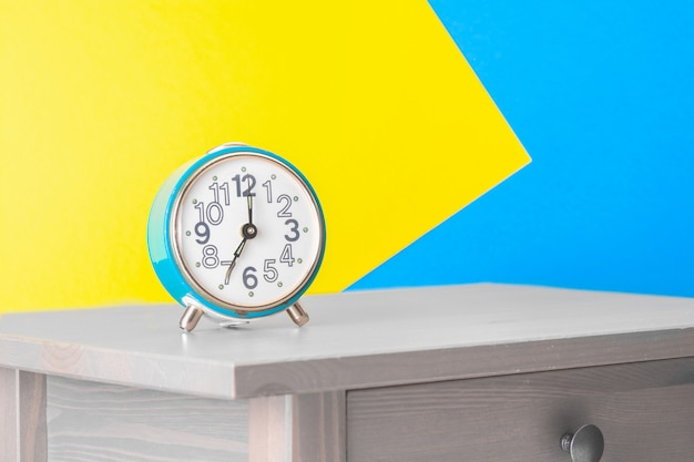 Turquoise retro alarm clock on the bedside table