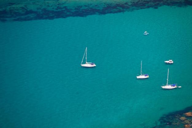 ターコイズブルーの海と白いヨット。上からの眺め