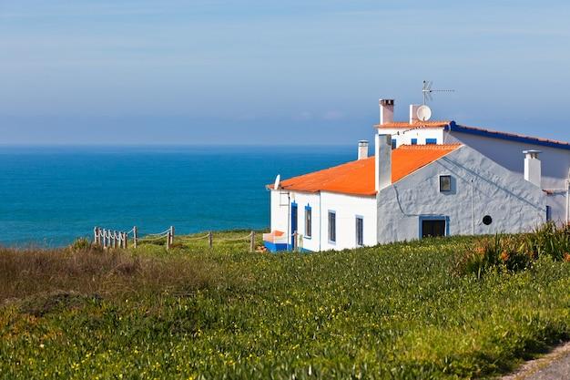 ポルトガルのターコイズブルーの海、青い空と白い家。横ショット