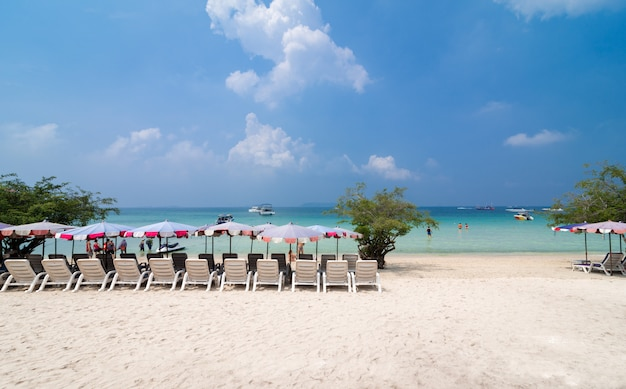 Turquoise sea, deckchairs, white sand and palms
