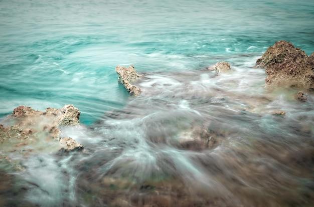 岩とかすんでいる海のあるターコイズブルーの海、長時間露光。グランドケイマン