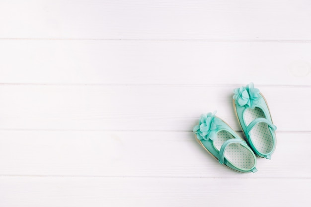 Turquoise shoes for baby girl over light wooden background with copy space