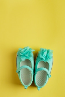Turquoise shoes for baby girl over yellow background
