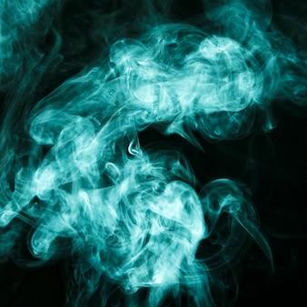 ターコイズ色の煙の雲が黒の背景に広がる