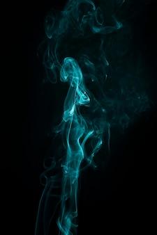 청록색 연기는 어두운 검은 배경에 넓게 퍼져 있습니다.