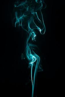 Бирюзовый дым кружится вверх на черном фоне