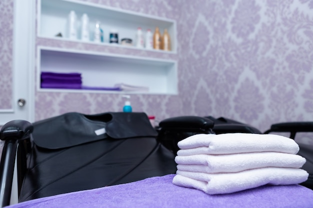 Turquoise spa towels pile on armchairs with washing stands in hairdressing salon.