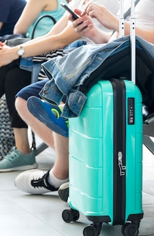 Turquoise suitcase with jacket resting on it