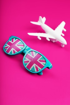 Turquoise sunglasses with united kingdom flag in lenses on crazy pink surface with white airplane
