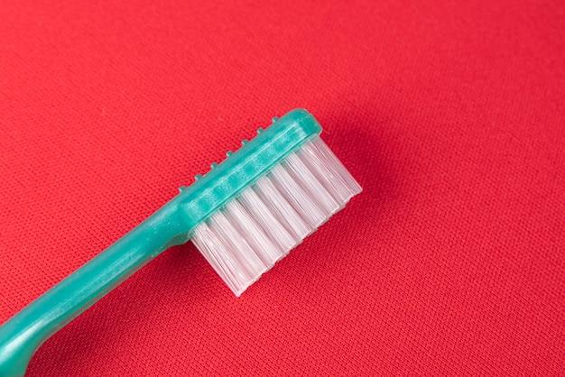 Бирюзовая зубная щетка на красной поверхности