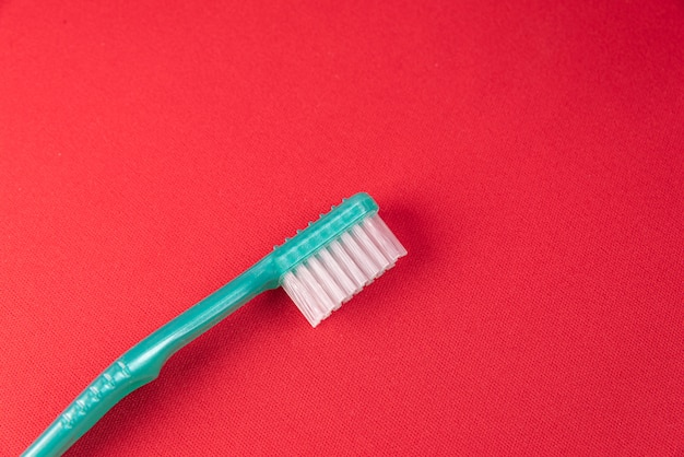 Turquoise toothbrush on the red surface
