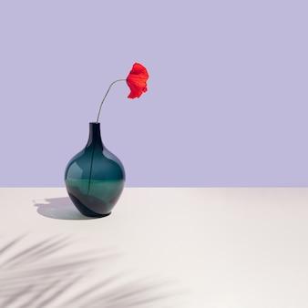 청록색 꽃병과 밝은 빨간색 꽃 파스텔 보라색 배경.