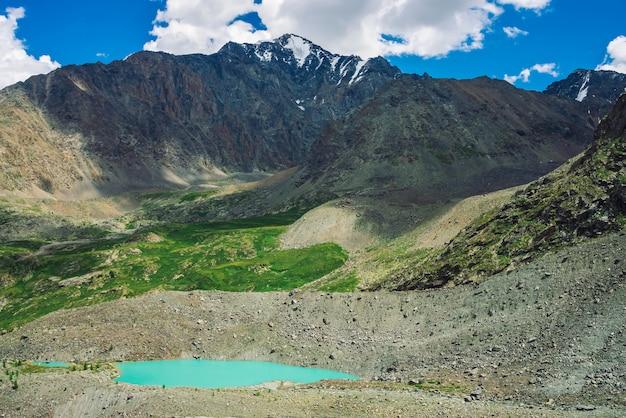 Turquoise water of mountain lake near huge rocky mountain