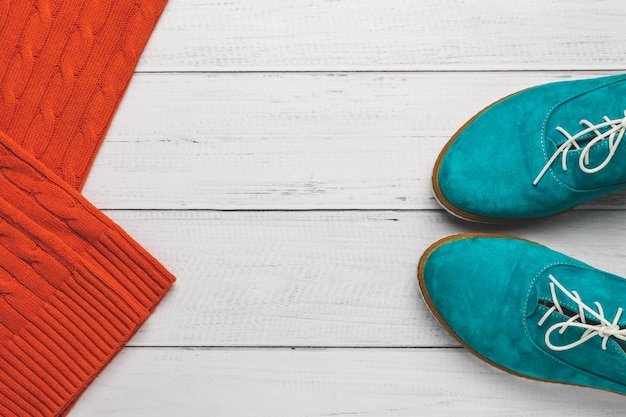 Turquoise women lace-up shoes and orange knitted sweater on wooden background.