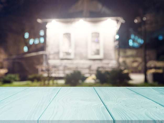 Turquoise wooden table in front of house at night