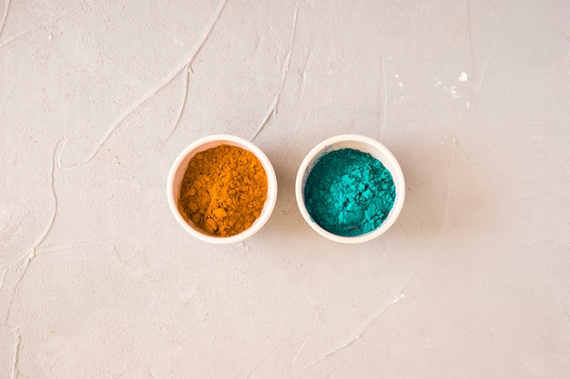 Turquoise and yellow holi color powder in the two bowl on concrete backdrop