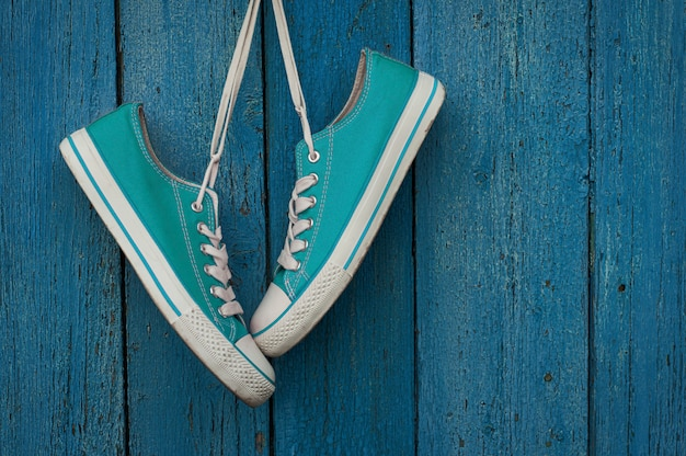 Turquoise youth sneakers hanging on a nail