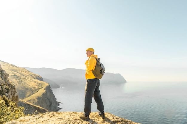 바다와 일몰을 배경으로 배낭을 메고 있는 tursit 남자. 여행 및 모험 개념입니다. 테스트를 위한 여유 공간.