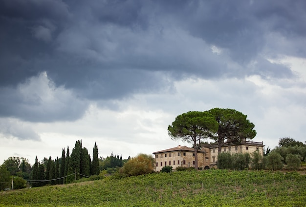 Tuscan hillside panorama with cloudy sky and typical local habitation.