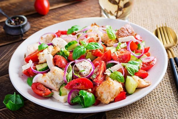Тосканский panzanella, традиционный итальянский салат с помидорами и хлебом на деревянных фоне. вегетарианский салат панзанелла. средиземноморская здоровая еда.