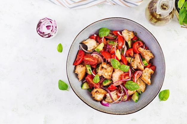 Тосканская панзанелла, традиционный итальянский салат с помидорами и хлебом. вегетарианский салат панзанелла. средиземноморская здоровая еда. вид сверху, копировать пространство