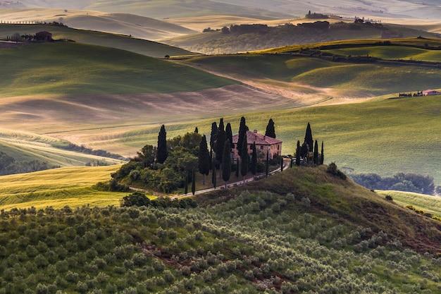伝統的な農家の丘と牧草地ヴァルドルチャイタリアのトスカーナの風景