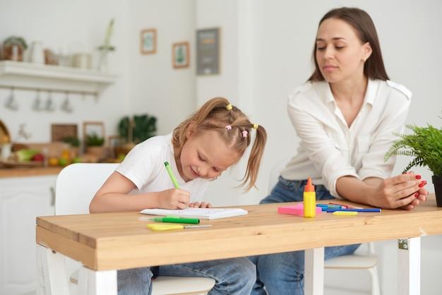 家庭教師と子供が台所で宿題をしています。ママと娘はその課題を解決しようとしています。彼らは良い気分と笑顔です。