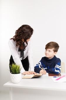 Репетитор и ученик сидят в белой комнате и выполняют задания для уроков.